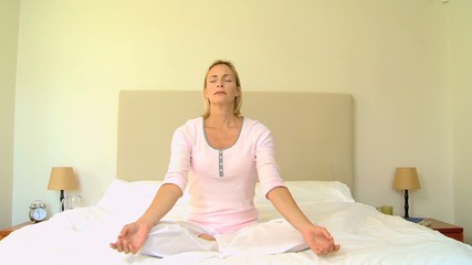 Blonde young woman doing meditation on a bed