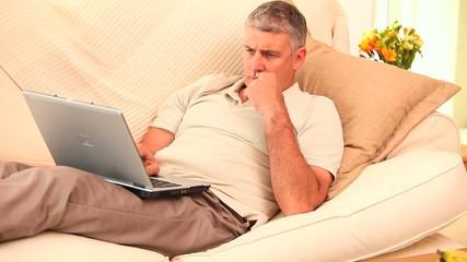 Man lying on sofa using laptop