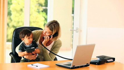 Mother doing office work with baby on her lap
