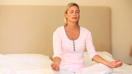 Young woman doing  mediation sitting on bed