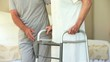 Male nurse helping woman to walk with a zimmer frame