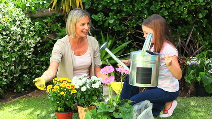 Mother and daughter watering potted plants in the garden