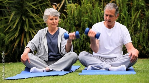 Senior couple doing  dumbell exercises on gym mats