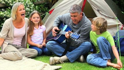 Father playing guitar and singing wih his wife and his children