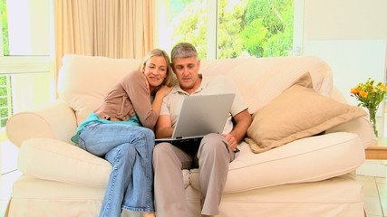 Young couple on sofa laughing over their laptop