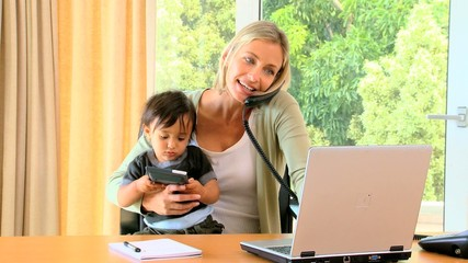 Woman carrying baby and working on  laptop