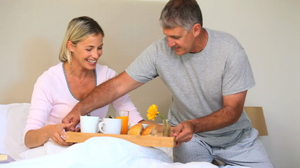 Man bringing his wife breakfast in bed