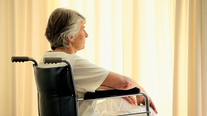 Mature woman in a wheelchair thinking