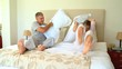 Young couple having pillow fight  on bed