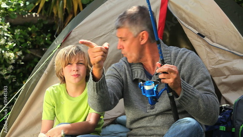 Man teaching his son how to fish
