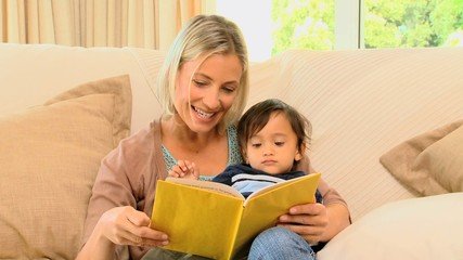 Woman reading a little book to her son
