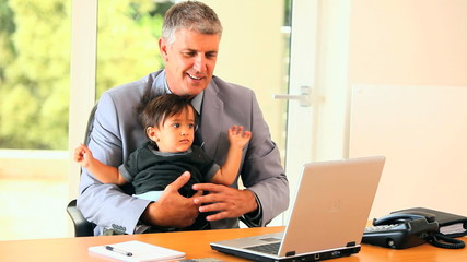 Businessman struggling with baby and laptop
