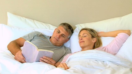 Man reading a book in bed with wife