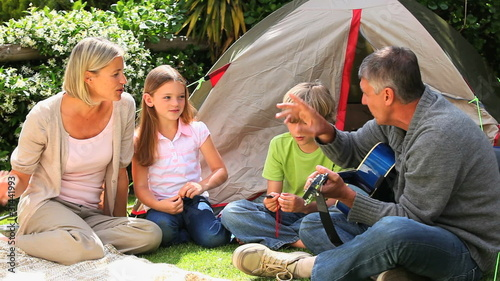Man playing guitar and singing with his family