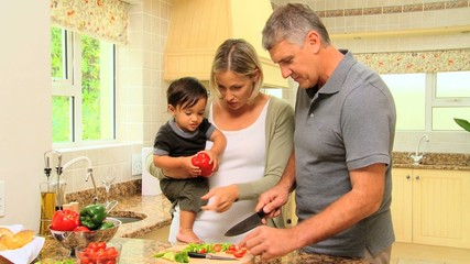 Cute little boy eating a sweet red peper while his father is cooking vegetables