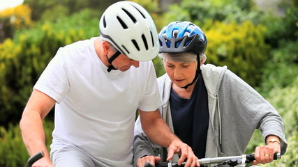 Mature couple riding bicycles outside