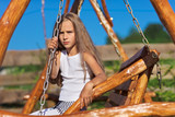Serious little girl with blond long hair sitting on wooden chain
