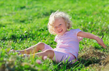 Cute little girl with blond curly hair playing jn green lawn wit