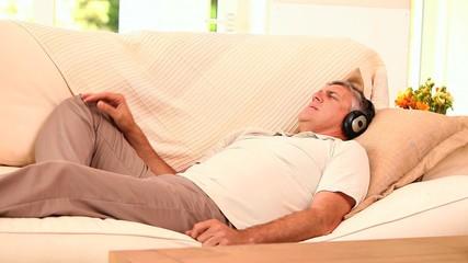 Man lying on sofa listening to music with headphones