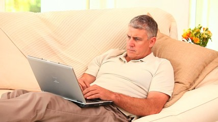 Man lying on couch using a laptop