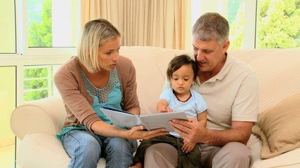 Parents reading a book for their little baby