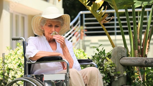 Woman in a wheelchair smelling a flower