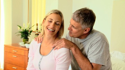 Attentive man massaging his wife's shoulders