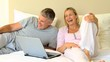 Couple on the bed with a laptop
