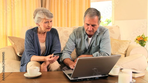 Elderly couple trying to buy something on internet