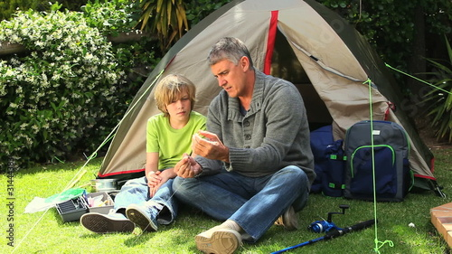 Father and son preparing a fishing rod