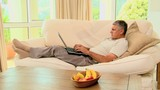 man Lying on sofa working
