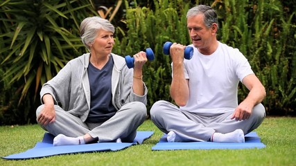 Dynamic mature couple with dumbbells