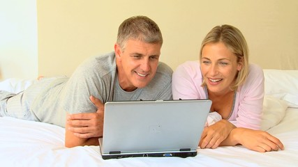 Couple lying down looking at a laptop