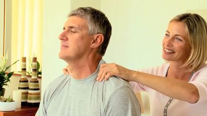 Woman massaging her husband's shoulders
