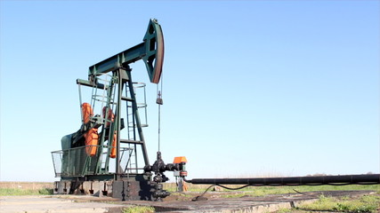 oilfield with pump jack and pipeline