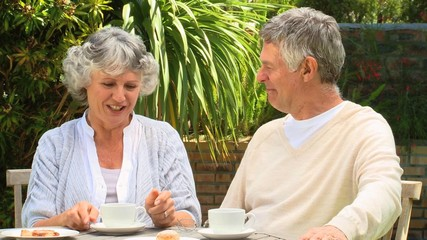 Mature couple having coffee in garden