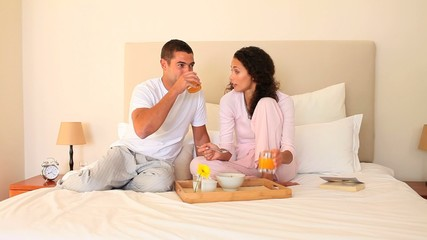 Young couple breakfasting on their  bed