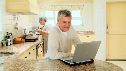Mature woman cooking while husband is working on a laptop