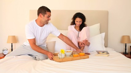 Man bringing breakfast in bed to his wife