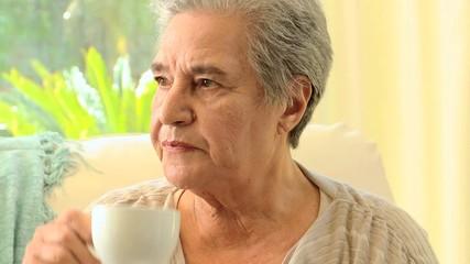 Pensive mature woman drinking tea