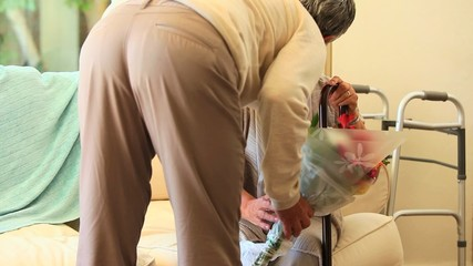Mature man bringing his wife a bunch of flowers in hospital