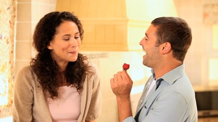 Happy young couple sharing a strawberry