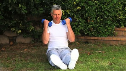 Man exercising his arms using dumbbells