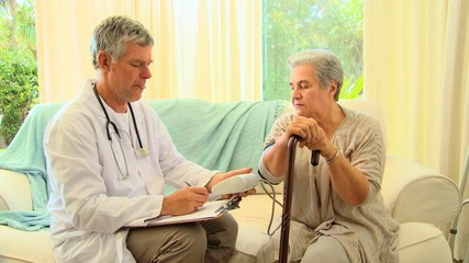 Doctor taking notes while taking his patient