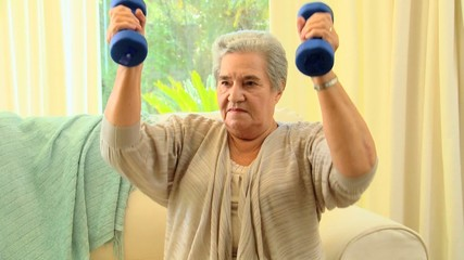 Mature woman exercising using dumbbells