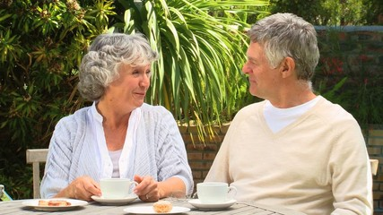 Mature couple having coffee in the garden