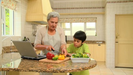 Woman cooking with her grandson