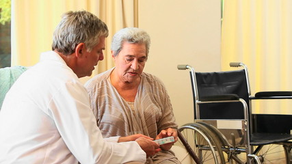 Doctor giving pills and instructions to his patient