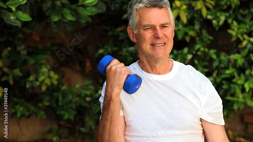 Mature man exercising with dumbells outdoors