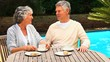 Retired couple having coffee outdoors